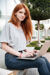 Beautiful redhead young woman sitting and using laptop outdoors