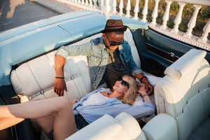 Beautiful relaxed young couple sitting and resting in cabriolet in summer