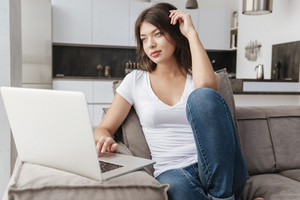 Beautiful relaxed young woman sitting and using laptop on sofa at home