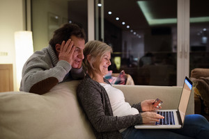Beautiful senior couple at home in their living room, woman with laptop sitting on couch shopping online