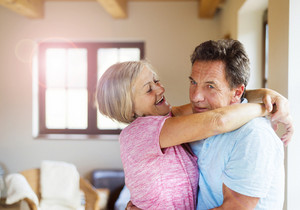 Beautiful senior couple in love embracing each other in their living room.