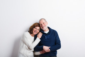 Beautiful senior couple in love hugging. Studio shot against white wall.