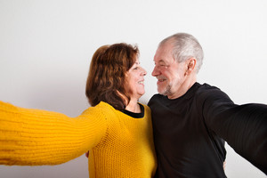 Beautiful senior couple in love hugging, taking selfie. Studio shot against white wall.
