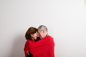 Beautiful senior couple in love hugging, wrapped in warm red blanket, touching foreheads. Studio shot against white wall.