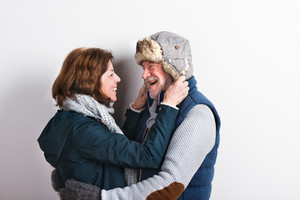 Beautiful senior couple in love in winter clothes, hugging. Studio shot against white wall.