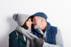 Beautiful senior couple in love in winter clothes, kissing. Studio shot against white wall.