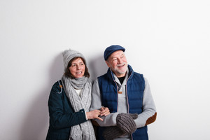 Beautiful senior couple in love in winter clothes. Studio shot against white wall.