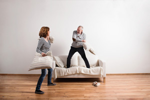 Beautiful senior couple in love standing on couch, having a pillow fight. Studio shot against white wall.