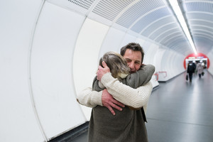 Beautiful senior couple in winter clothes in the hallway of subway in Vienna hugging