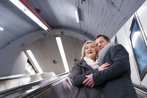 Beautiful senior couple in winter clothes standing at the escalator in Vienna subway