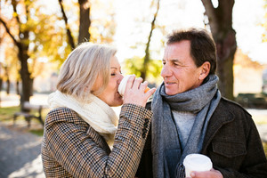 Beautiful senior couple on a walk in park, hugging, drinking coffee. Sunny day in autumn park.