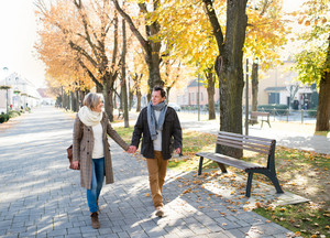 Beautiful senior couple on a walk in park. Sunny day in autumn park.