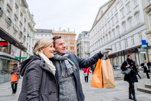 Beautiful senior couple shopping in historical centre of the city of Vienna, Austria. Winter. Man pointing at somoething with finger.