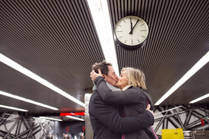 Beautiful senior couple standing at the underground platform, hugging and kissing. Welcoming or saying good bye. Five past twelve.