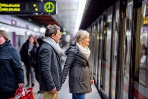 Beautiful senior couple standing at the underground platform, waiting, entering the train