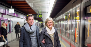Beautiful senior couple standing at the underground platform, waiting
