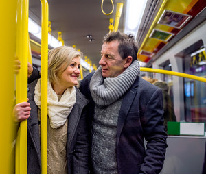 Beautiful senior couple standing in a crowded subway train