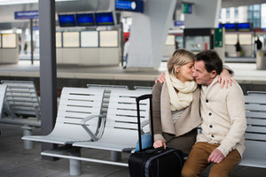 Beautiful senior couple waiting on train station, sitting on bench, hugging and kissing.