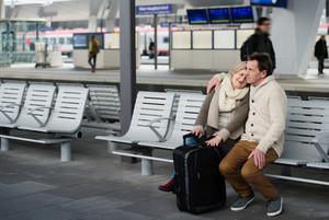 Beautiful senior couple waiting on train station, sitting on bench, hugging.
