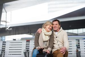 Beautiful senior couple waiting on train station, sitting on bench, hugging