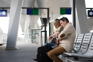 Beautiful senior couple waiting on train station, sitting on bench, looking at watch.