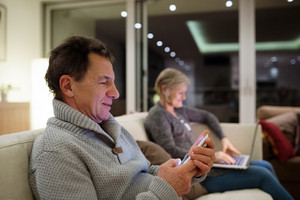 Beautiful senior couple with laptop and smart phone at home in their living room sitting on couch