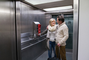 Beautiful senior couple with luggage standing in modern elevator. People travelling.