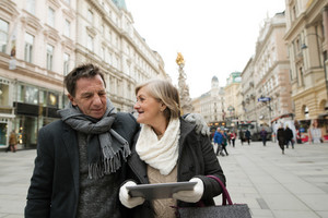 Beautiful senior couple with tablet on a walk in historical centre of the city of Vienna, Austria. Winter.