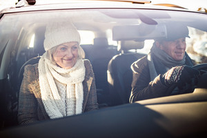 Beautiful senior woman and man in winter clothes driving a car