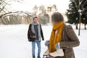 Beautiful senior woman and man in winter nature with ice skates going to outdoor rink.