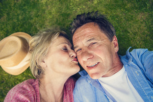 Beautiful senior woman and man lying on the gras taking selfie