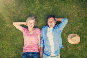 Beautiful senior woman and man lying on the gras