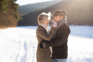 Beautiful senior woman and man on a walk in sunny winter nature hugging.