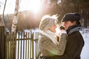 Beautiful senior woman and man on a walk in sunny winter nature, hugging