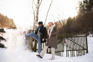 Beautiful senior woman and man on a walk in sunny winter nature, kicking snow.