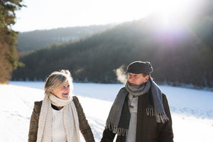 Beautiful senior woman and man on a walk in sunny winter nature.