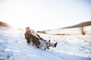 Beautiful senior woman and man on sledge having fun in sunny winter nature.