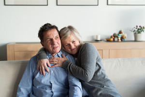 Beautiful senior woman and man sitting on a couch in living room, hugging