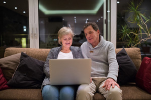 Beautiful senior woman and man sitting on a couch in living room, working on laptop