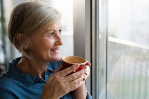 Beautiful senior woman at home standing at the window in her living room holding a cup of coffee or tea, smiling