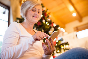 Beautiful senior woman holding smart phone, texting, sitting in front of illuminated Christmas tree inside in her house.
