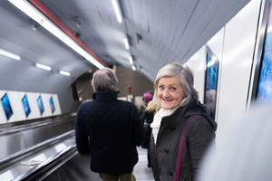 Beautiful senior woman in black coat and white woolen scarf standing at the escalator in Vienna subway