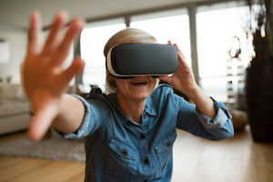 Beautiful senior woman in denim shirt at home in her living room wearing virtual reality goggles, reaching to someone