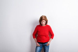 Beautiful senior woman in red woolen sweater, hands in pockets, looking down. Studio shot against white wall.