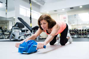 Beautiful senior woman in sports clothing in gym exercising with wheel roller for abs on floor as part of fitness training.