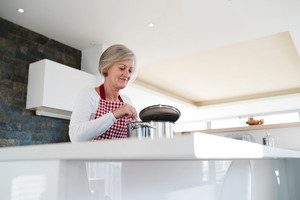 Beautiful senior woman in the kitchen cooking, mixing food in a pot.