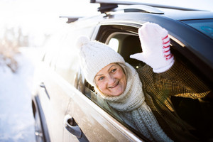 Beautiful senior woman in winter clothes in a car, waving