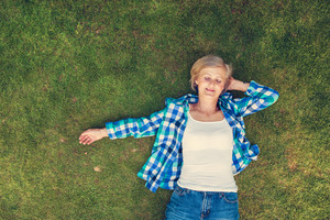 Beautiful senior woman lying on a grass in a park