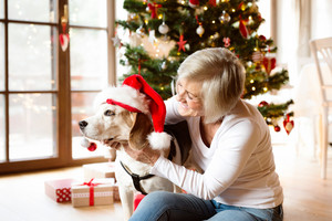 Beautiful senior woman sitting on the floor in front of Christmas tree with her dog wearing red Santa hat snuggling.
