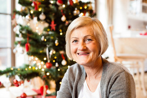 Beautiful senior woman sitting on the floor in front of illuminated Christmas tree inside in her house.